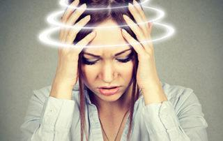 woman holding her head suffering from dizziness and vertigo