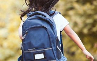 young child with backpack going to school