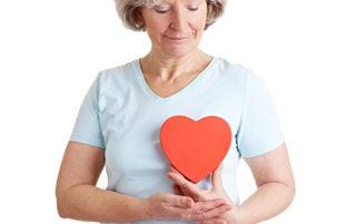 Woman holding paper heart for heart health